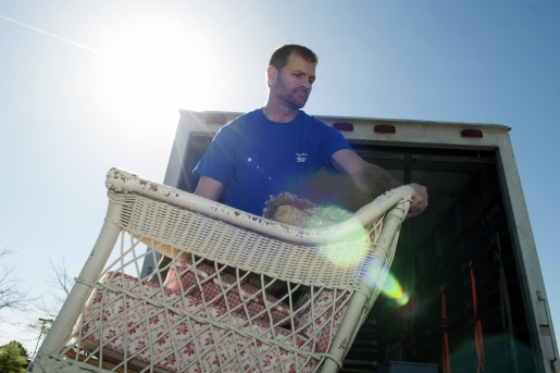 A man unloads a white wicker chair off of a truck